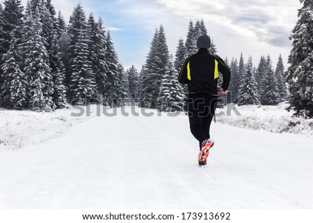Man in Winter Jogging - stock photo