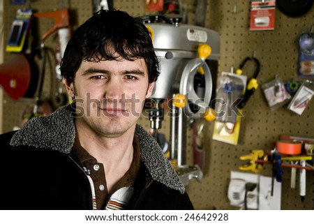 Man in workshop smiling at a the camera - stock photo