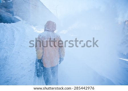Man in yellow jacket with snow removal machine walks on a snowy valley in clouds of ice spray. Snowy winter illustration - stock photo