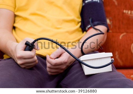 Man in yellow shirt is checking his blood pressure (focus on hands)