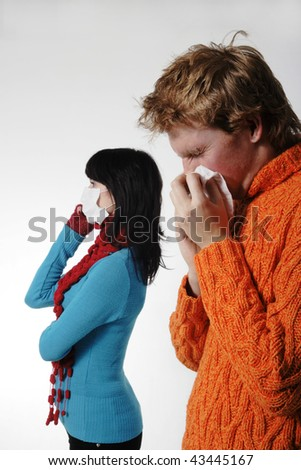 Man influenza patients, a woman stands behind a mask, said by telephone, A(H1N1), on the grey background. Focus is on the man