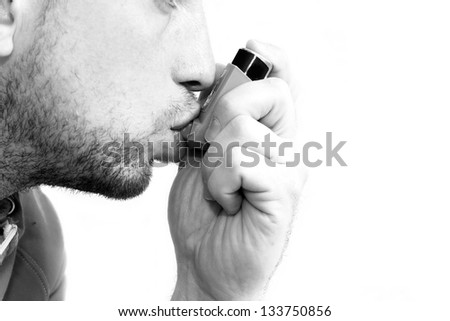 man inhaling his asthma pump - stock photo