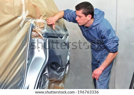 Man inspecting newly painted car. - stock photo