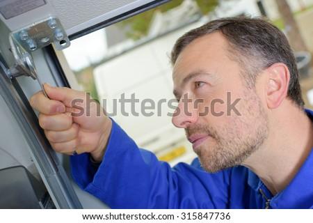 Man installing a garage door - stock photo