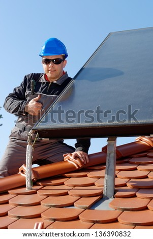 Man installing alternative energy photovoltaic solar panels on roof/ Thumbs up - stock photo