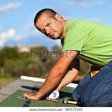 Man installing bitumen roof shingles - taking measurements for the last row - stock photo