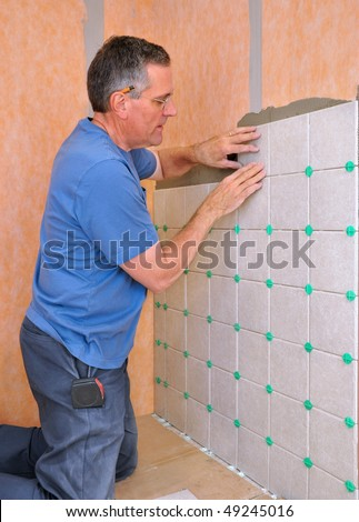 Man installing ceramic tile in shower area of bathroom - stock photo