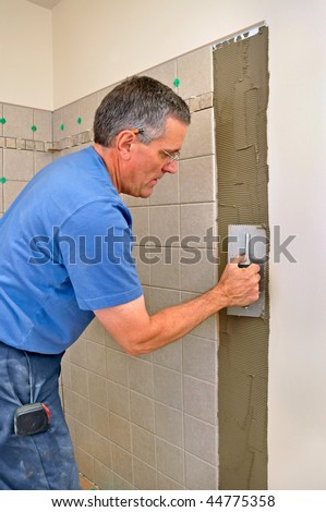 Man installing ceramic tiles in bathroom - stock photo