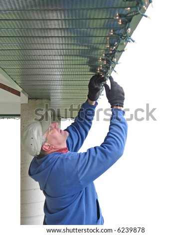 Man installing Christmas lights - stock photo
