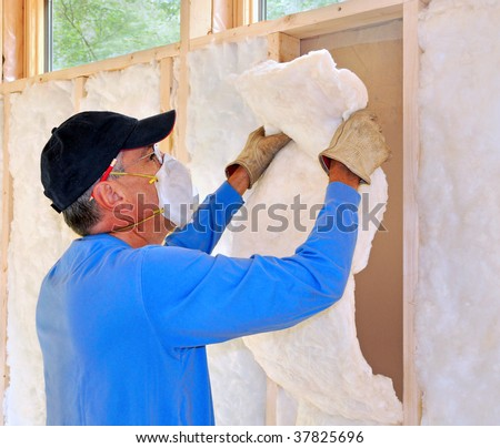 Man installing fiberglass insulation - stock photo