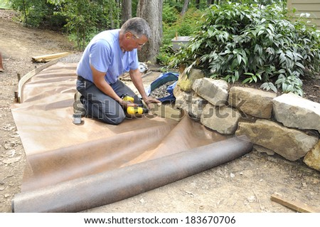 Man installing gravel path in garden - stock photo