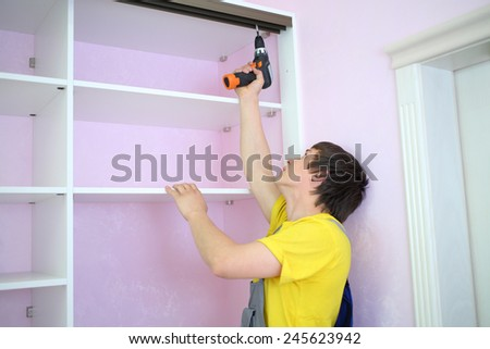 Man installing guide rails for sliding wardrobe in room with pink walls - stock photo