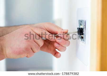 Man installing light switch with screwdriver after home renovation - stock photo