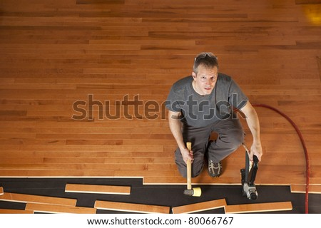 Man installing planks of hardwood floor