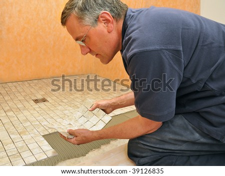 Man installing sheet of mosaic ceramic tiles on shower floor - stock photo