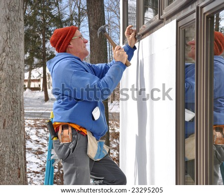 Man installing window in new addition - stock photo