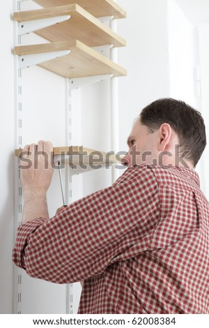 Man installing wooden shelves on brackets