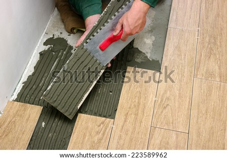 Man installs a ceramic tile  - stock photo