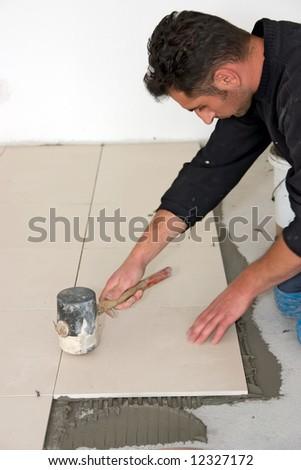 Man installs ceramic tile - stock photo