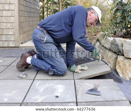 Man installs flagstone pavers on patio - stock photo