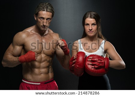 Man Instructor And Woman Training Mixed Martial Art - Bodybuilding Couple Posing With Boxing Gloves On Black Background - stock photo