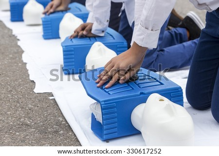 man instructor showing CPR on training doll - stock photo