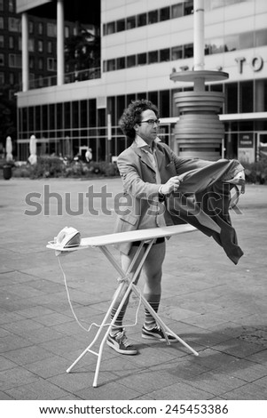 Man ironing his suit in the city in a business area in front of office buildings - stock photo