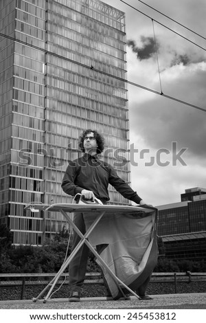 Man ironing his suit in the city in front of office building, business area - stock photo