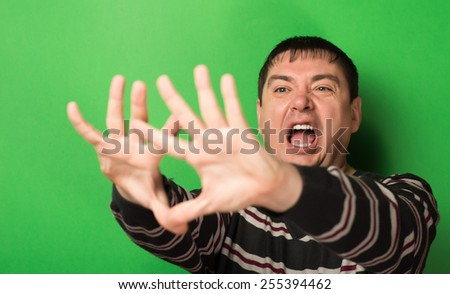 man is afraid gesture, hands on a green background - stock photo