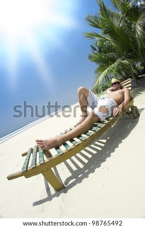 Man is chilling in the sun on a beautiful beachside. - stock photo