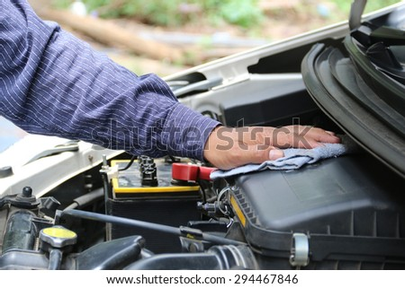 Man is cleaning his car engine with a rag. - stock photo
