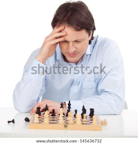 Man is concentrated over his chess board - stock photo