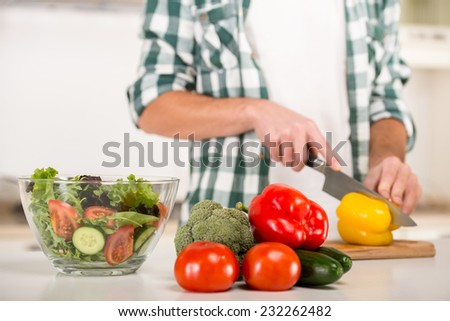 Man is cooking vegetable salad in the kitchen. - stock photo