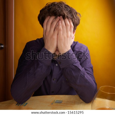 man is covering his face with hands - stock photo