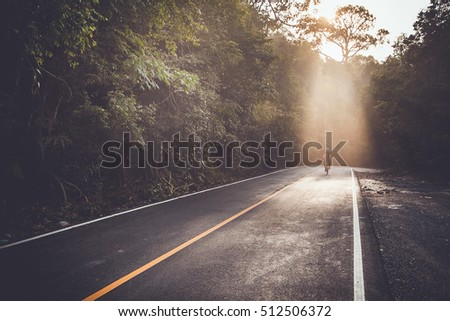 Man is cycling on forest road in the evening,vintage color tone