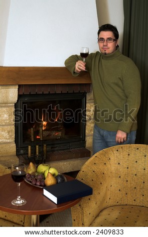 Man is drinking a glass of wine by the fireplace and looks at the camera. - stock photo