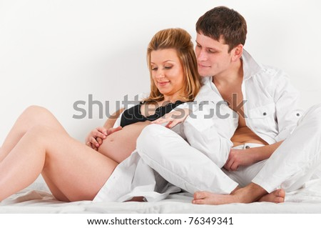 man is embracing his pregnant wife in bed at morning