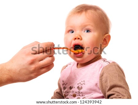 man is feeding his baby with a spoon