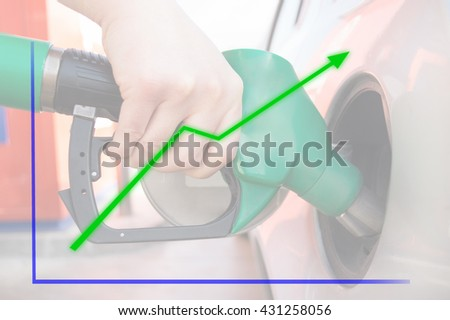 man is filling he petrol tank of the car at gas station with a growth chart in background as concept of price is increasing - stock photo