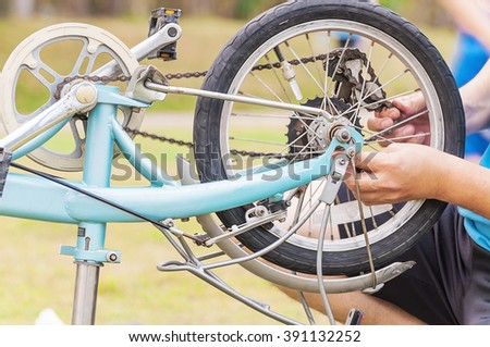 Man is fixing bicycle, selective focused. - stock photo