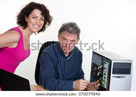 Man is fixing computer with woman watching it  - stock photo