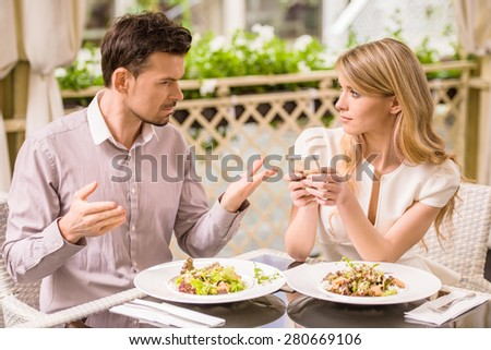 Man is getting nervous in restaurant while his woman looking at phone. - stock photo