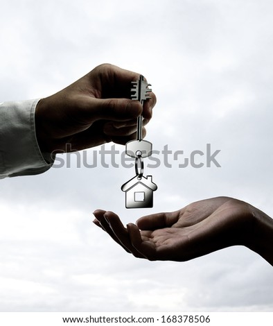 Man is handing a house key to a woman - stock photo