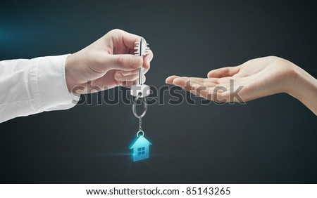 Man is handing a house key to a woman.Key with a key chain in the shape of the house. On a black background - stock photo