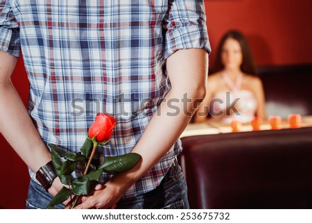 Man is hiding a red rose to make a gift to his girl at their dating.