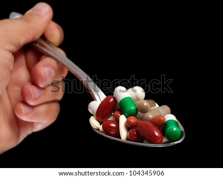 Man is holding a spoon full of various drug pills. - stock photo