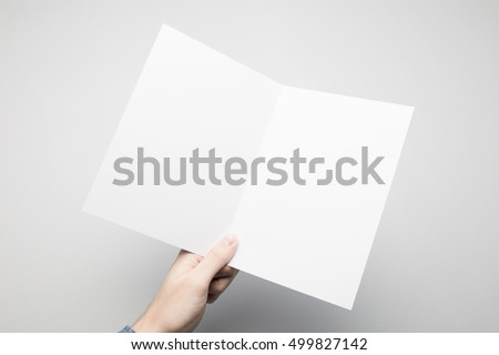 Man is holding a white Bi-Fold paper flyer.