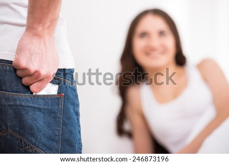Man is holding condom behind his back just before sex. - stock photo