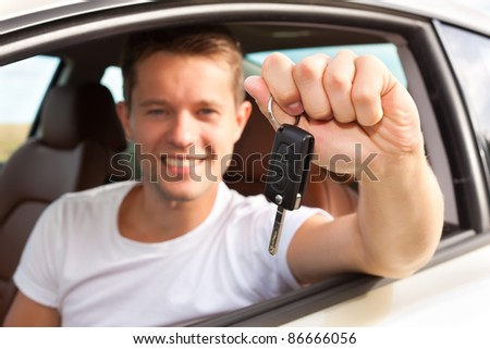 Man is holding his car key sitting himself in the automobile and obviously has fun - stock photo