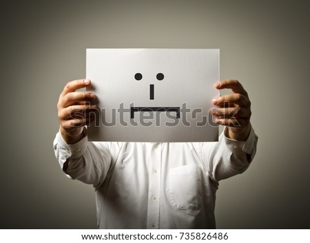 Man is holding white paper with smile. Embarrassed and confused concept.